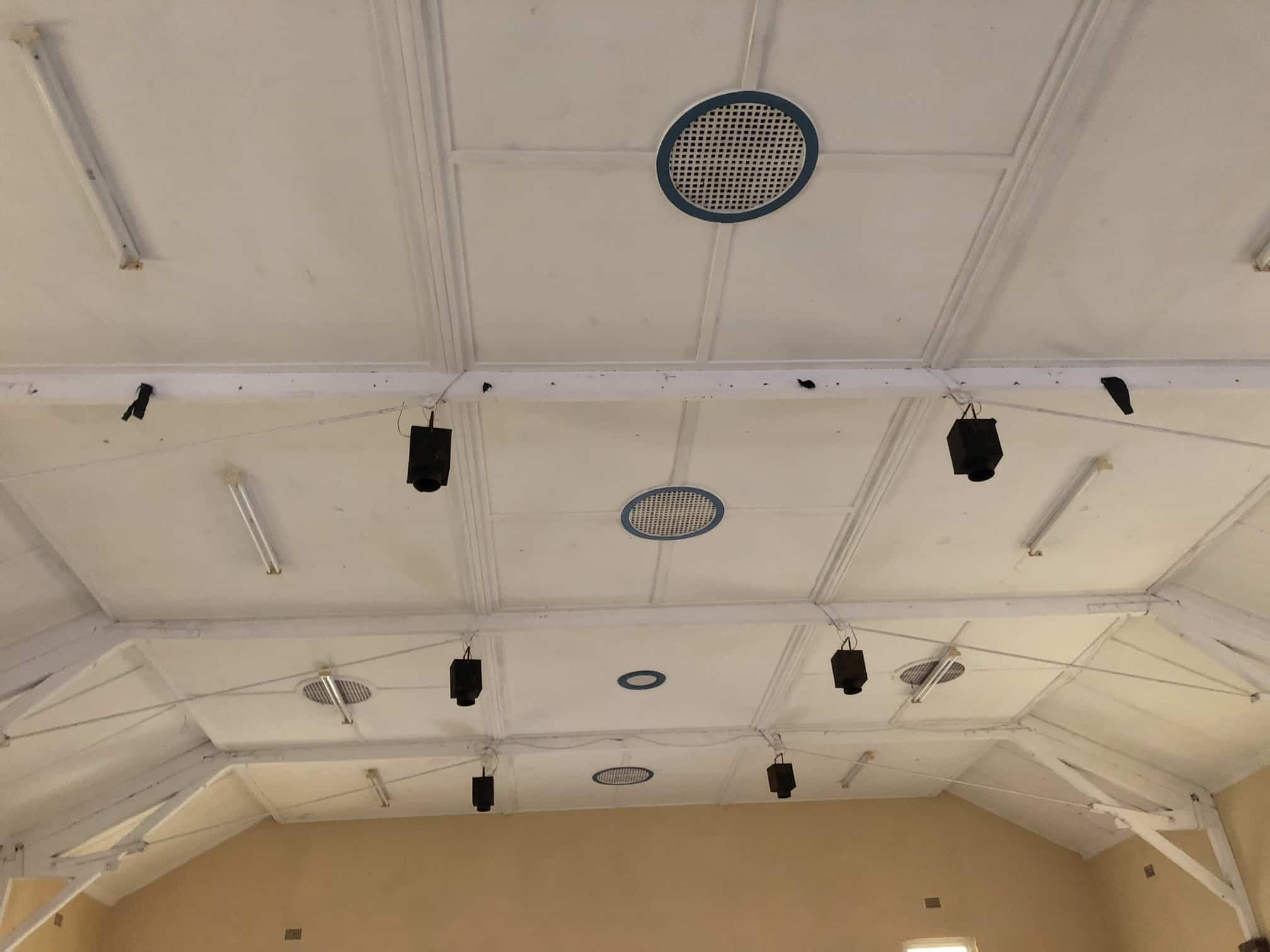 white ceiling with 4 air outlets and a few ceiling lights
