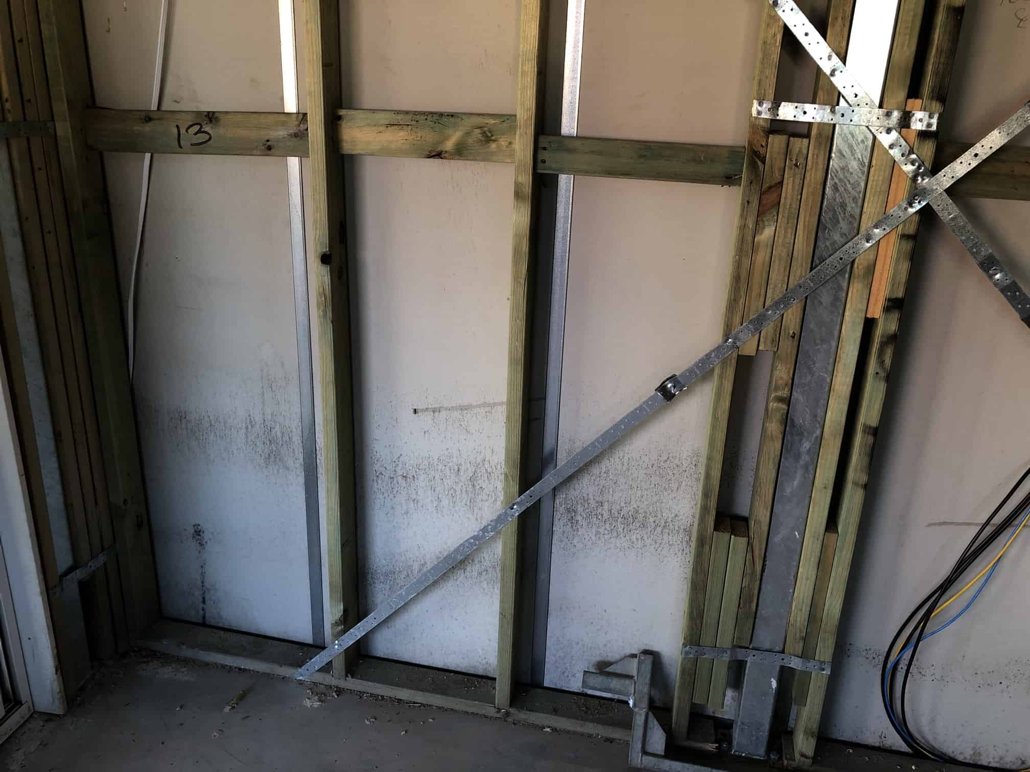 mould covered internal wall with metal and wood frame